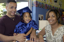 Proud parents posing with developmentally disabled child in graduation gown