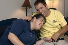 Two developmentally disabled adults laugh affectionately together