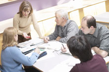 Small group of professionals gather around a table to review materials
