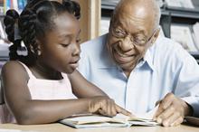 A young girl learning to read with the help of an elderly man