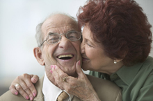 An older woman kisses an older man on the cheek