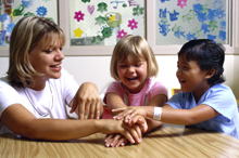 A woman playing a game with two children