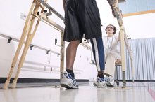 A physical therapist helps a man with a prosthetic leg learn to walk
