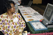 Woman sitting at a job fair table using a screen magnifier