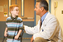 Doctor talking to young boy using forearm crutches